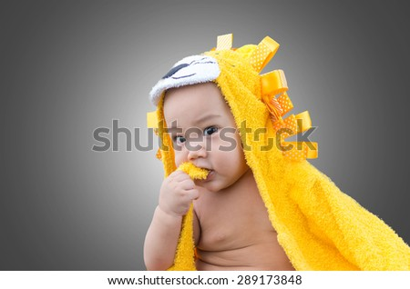 Portrait of happy asian baby on gray background - stock photo
