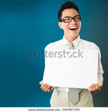 Portrait of happy Asian businessman with white board - stock photo