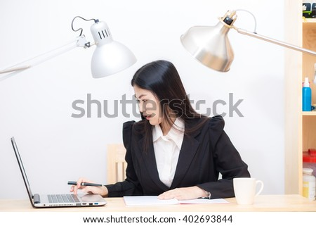 Portrait of happy asian businesswoman  sitting at her workplace in office with laptop - stock photo