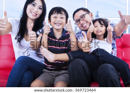 Portrait of happy asian family sitting on couch and showing thumbs up