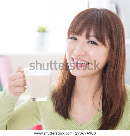 Portrait of happy Asian girl drinking dairy milk as breakfast. Young woman indoors living lifestyle at home.