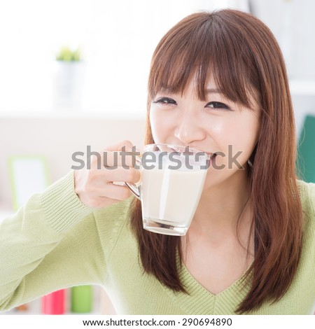 Portrait of happy Asian girl drinking milk as breakfast. Young woman indoors living lifestyle at home.