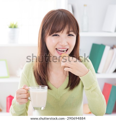 Portrait of happy Asian girl eating cookies and having soymilk as breakfast. Young woman indoors living lifestyle at home.