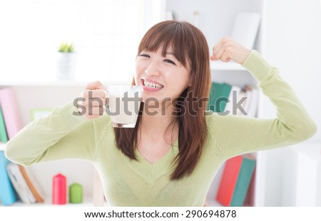 Portrait of happy Asian girl showing strong arm while drinking milk as breakfast. Young woman indoors living lifestyle at home.