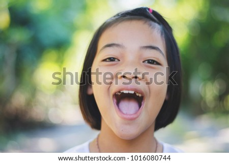 Portrait of Happy Asian girl smiling out door in forest