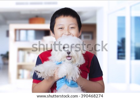 Portrait of happy Asian little boy playing and holding a maltese dog at home