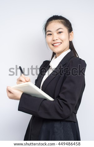 Portrait of happy asian smiling business woman with booklet wear blacksuit on white background - stock photo