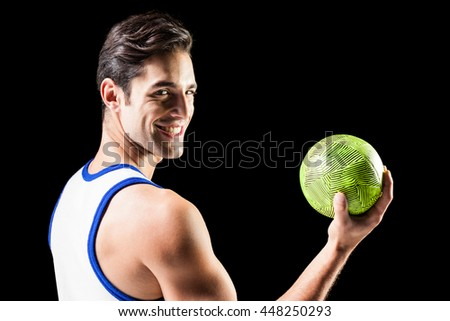 Portrait of happy athlete man holding ball on black background