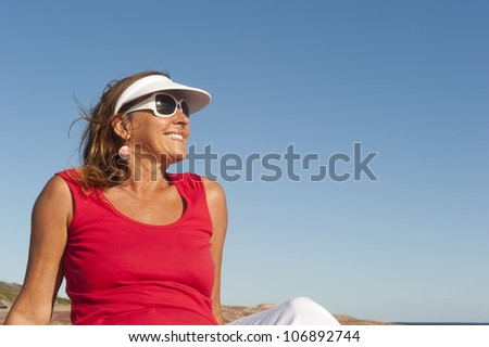 Portrait of happy attractive looking middle aged woman joyful laughing, isolated with sunshine on face, ocean and blue sky as background and copy space. - stock photo
