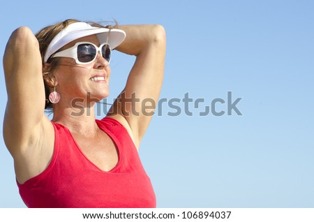 Portrait of happy attractive looking middle aged woman joyful laughing, isolated with sunshine on face and sky as background and copy space.