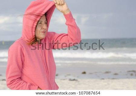 Portrait of happy attractive looking middle aged woman wearing pink sweater, standing at beach, isolated with storm clouds and ocean as background and copy space. - stock photo