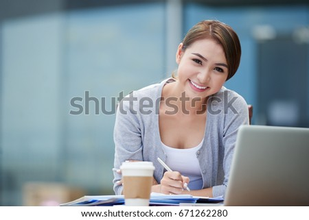 Portrait of happy attractive Vietnamese business lady sitting at tablet outdoors
