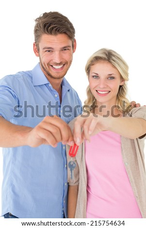 Portrait of happy attractive young couple holding new house key over white background - stock photo