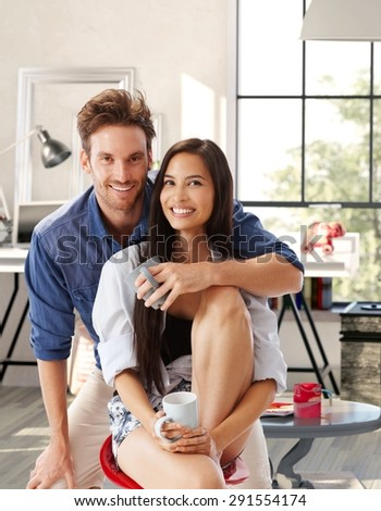Portrait of happy attractive young loving couple at home, hugging, looking at camera. - stock photo