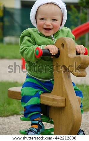 Portrait of happy baby boy jumping on a wooden horse on a playground. Child concept.  - stock photo