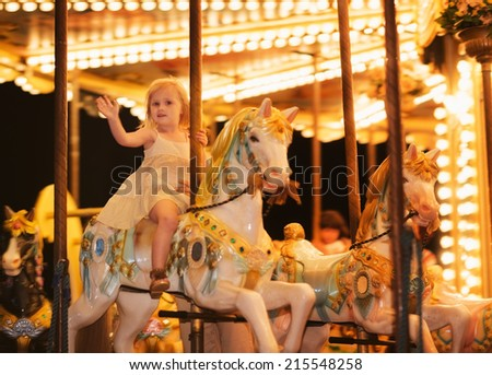 Portrait of happy baby girl riding on carousel - stock photo