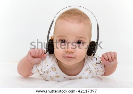 Portrait of happy baby with headphones on white background - stock photo