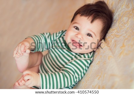 Portrait of happy beautiful baby on the bed in his room.