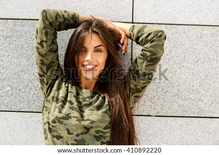 Portrait of happy beautiful brunette woman with long sexy healthy hair in khaki top and ripped jeans with wooden longboard skateboard look to camera and smile. Urban scene, city life. Hipster lady. - stock photo