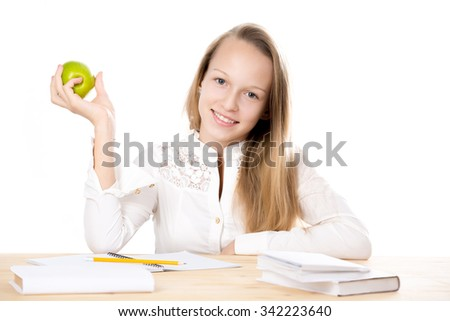 Portrait of happy beautiful casual caucasian girl wearing white shirt, sitting at the desk, doing homework, studying, holding fresh green apple in hand, isolated studio shot, white background - stock photo