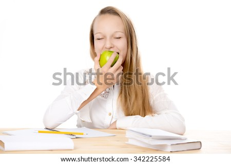 Portrait of happy beautiful casual caucasian girl wearing white uniform shirt, sitting at the desk, doing homework, studying, biting fresh green apple, isolated studio shot, white background - stock photo