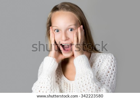 Portrait of happy beautiful casual caucasian teenage girl wearing white knitted sweater screaming with excited surprised facial expression, wide opened eyes and mouth, studio image, gray background - stock photo