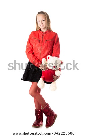 Portrait of happy beautiful casual teenage girl in red leather jacket holding teddy bear, friendly smiling, looking at camera with cheerful expression, isolated, studio, white background - stock photo