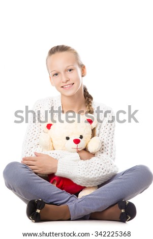 Portrait of happy beautiful casual teenage girl sitting cross-legged in knitted sweater hugging teddy bear, friendly smiling, looking at camera with cheerful expression, studio, white background - stock photo