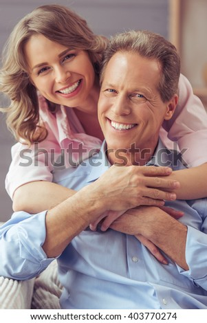 Portrait of happy beautiful couple cuddling, looking at camera and smiling while sitting on sofa - stock photo