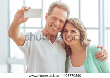 Portrait of happy beautiful couple in casual clothes cuddling, making a selfie and smiling - stock photo