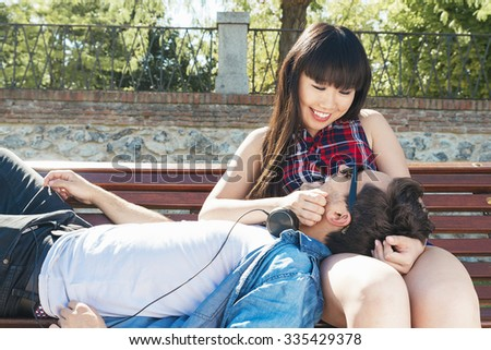 Portrait of happy beautiful couple isolated on street. Caucasian and chinese on the bench at park - stock photo