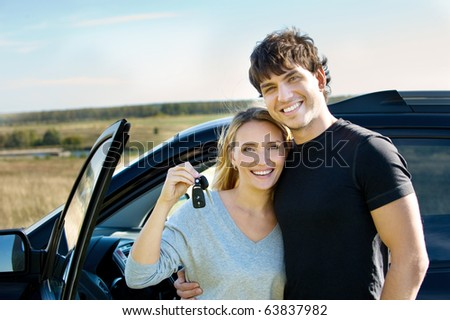 portrait of happy beautiful couple showingh the keys standing near the car - stock photo