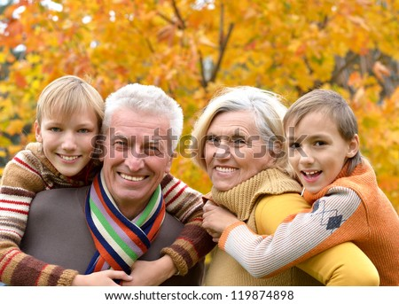 portrait of happy beautiful elderly couple and grandchildren together resting - stock photo