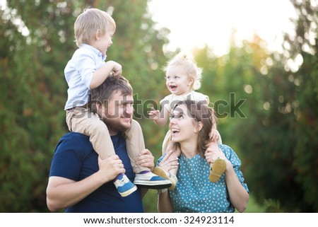 Portrait of happy beautiful family of four walking in park in summer. Mom and dad carrying two little cheerful laughing kids on shoulders. Parents and siblings playing, having fun together - stock photo
