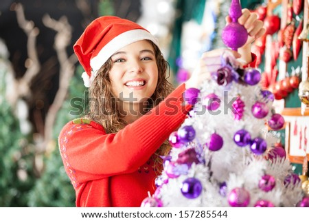 Portrait of happy beautiful female owner decorating Christmas tree in store - stock photo