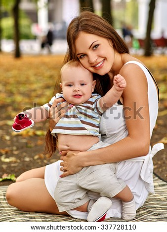 Portrait of happy beautiful mother and her baby summer sitting outdoors in park on weekend. - stock photo