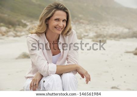 Portrait of happy beautiful woman relaxing at beach