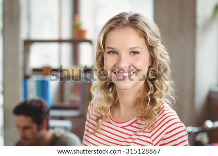 Portrait of happy beautiful woman standing in creative bright office