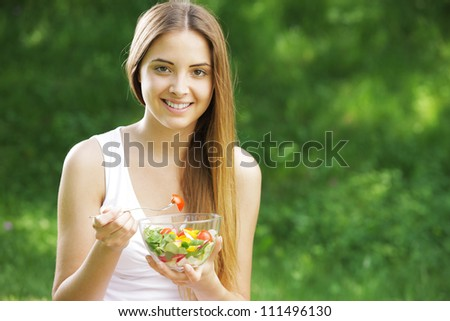 Portrait of happy beautiful young woman eating vegetable salad