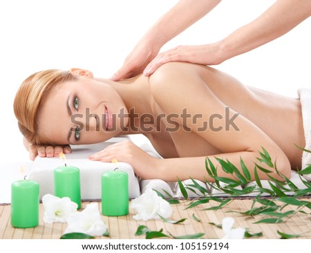 portrait of happy beautiful young woman getting back massage at spa