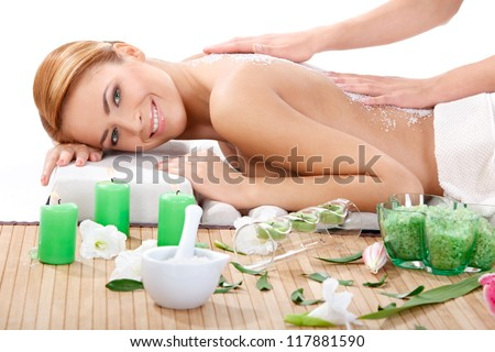 portrait of happy beautiful young woman getting back massage with sea salt at spa
