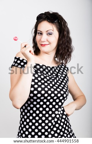 Portrait of happy beautiful young woman licking sweet candy. pretty woman with heart shaped lollipop. - stock photo