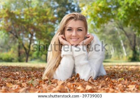 Portrait of happy beautiful young woman lying on leaves outdoors.  Autumn environment. - stock photo