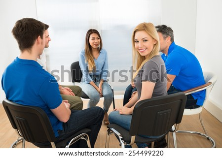 Portrait Of Happy Beautiful Young Woman Sitting With Her Friends - stock photo
