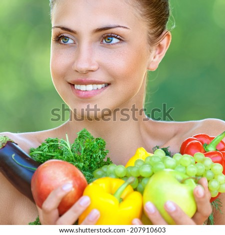 Portrait of happy beautiful young woman with vegetables, against background of summer green park.