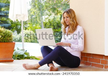 Portrait of happy blogger writing her blog at laptop while sitting at garden at home.  - stock photo