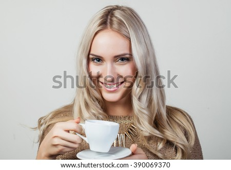 Portrait of happy blond woman holding white cup - stock photo