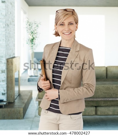 Portrait of happy blonde businesswoman smiling, looking at camera, holding folder.