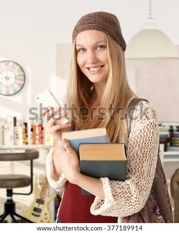 Portrait of happy blonde college student holding books, using mobile, looking at camera. - stock photo