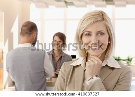 Portrait of happy bond businesswoman at office, looking at camera, smiling.